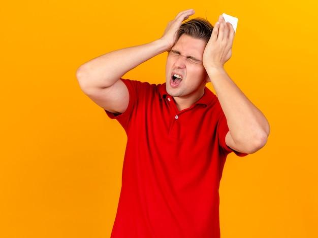 Bolący młody przystojny blondyn chory trzymający serwetkę trzymając ręce na głowie cierpiącej na ból głowy z zamkniętymi oczami odizolowanymi na pomarańczowej ścianie z miejscem na kopię