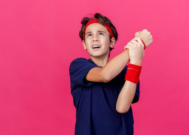 Bolący młody przystojny chłopak sportowy noszący opaskę i opaski na rękę z aparatami ortodontycznymi patrząc w górę trzymając nadgarstek odizolowany na szkarłatnej ścianie