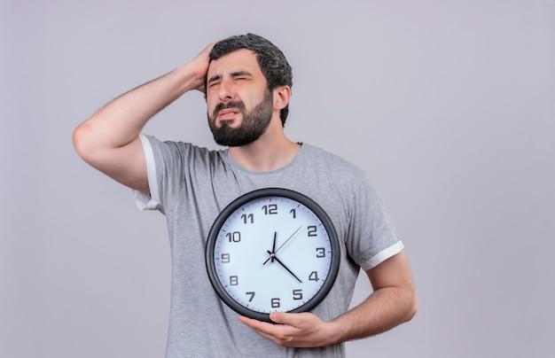 Bolący młody przystojny kaukaski mężczyzna trzyma zegar kładąc rękę na głowie cierpiącej na ból z zamkniętymi oczami na białym tle z miejsca na kopię