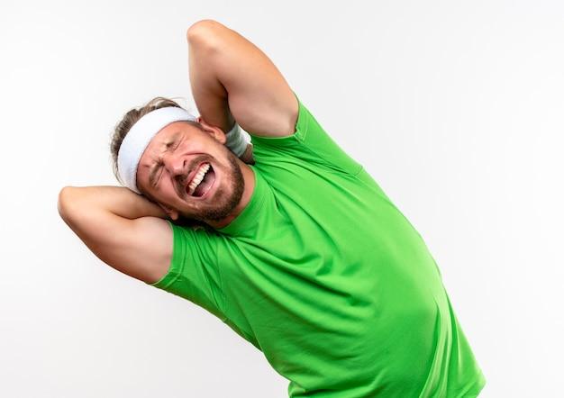 Bolący młody przystojny sportowy mężczyzna nosi opaskę i opaski, kładąc ręce za plecami z zamkniętymi oczami i otwartymi ustami na białym tle na białej ścianie