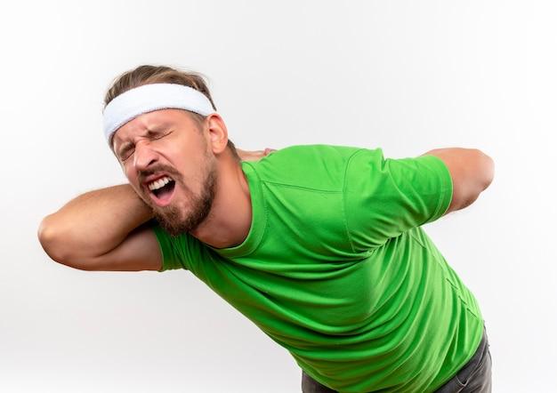 Bolący młody przystojny sportowy mężczyzna nosi opaskę i opaski, kładąc ręce za plecami z zamkniętymi oczami na białym tle na białej ścianie