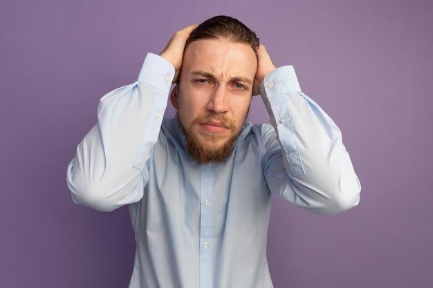 Bolący przystojny blondyn trzyma głowę na białym tle na fioletowej ścianie