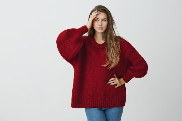 Bolała mnie głowa od nudnych rozmów. salowy portret piękna dziewczyna trzyma palmę na czole w zimowym pulowerze i stoi z zmęczonym i wyczerpanym wyrażeniem