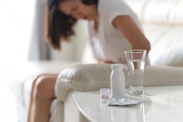 Bolesna choroba żołądka obolałość kobieta siedzi na kanapie w domu.
