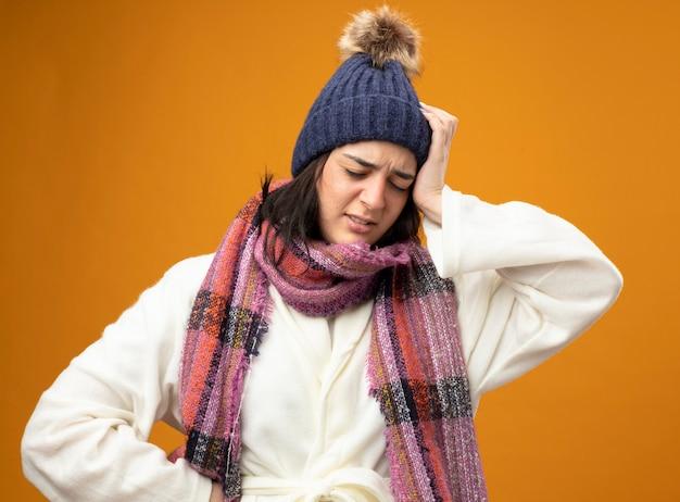 Bolesna młoda kaukaska chora dziewczyna w szacie zimowej czapce i szaliku kładzie rękę na głowie, trzymając drugą w talii z zamkniętymi oczami odizolowanymi na pomarańczowej ścianie