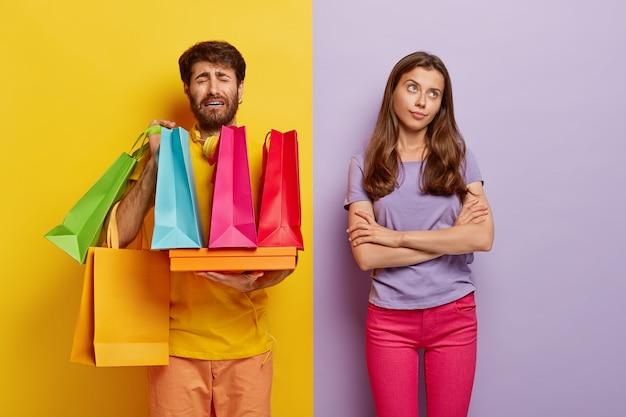 Bolesny niezadowolony mężczyzna przeładowany kolorowymi torbami na zakupy, zmęczony wielogodzinnym chodzeniem po różnych sklepach, obojętna kobieta trzyma ręce skrzyżowane, nie pomaga mężowi nosić paczki