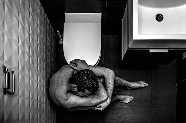 Bolesny obraz młodego mężczyzny siedzącego na podłodze w toalecie i cierpiącego