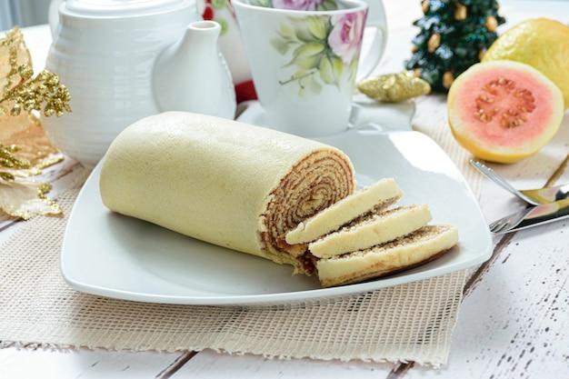 Bolo de rolo roll cake w plasterkach obok dekoracji świątecznej tradycyjny brazylijski cukierek z boku.