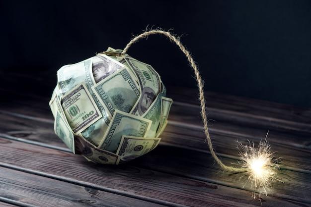 Bomba pieniędzy banknotów stu dolarowych z płonącym knotem. niewiele czasu przed wybuchem