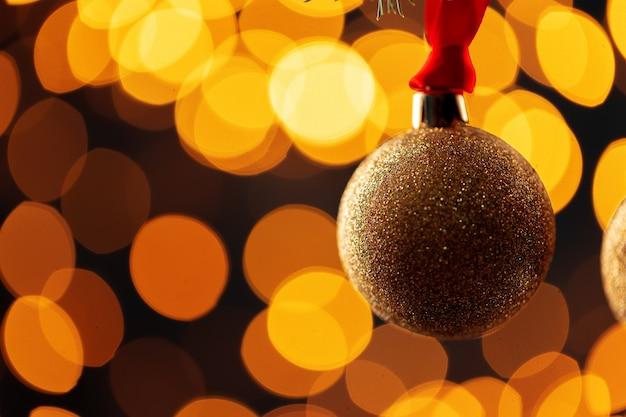 Bombka bożonarodzeniowa przed niewyraźnymi światłami girlandy