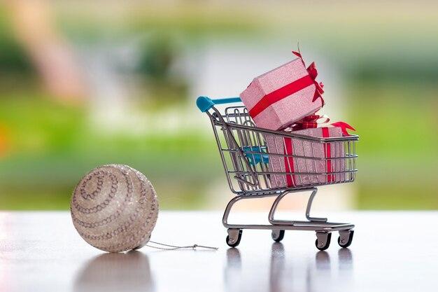 Bombka i koszyk z prezentami na niewyraźne tło, koncepcja świątecznych zakupów, cocus na wózku