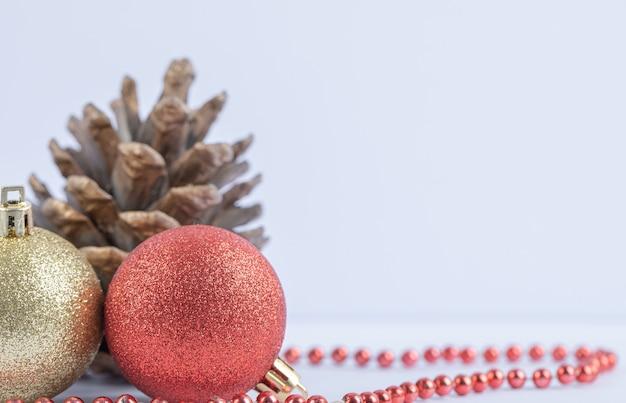 Bombki choinkowe i dębowe szyszki z czerwonym łańcuszkiem z pereł na białym