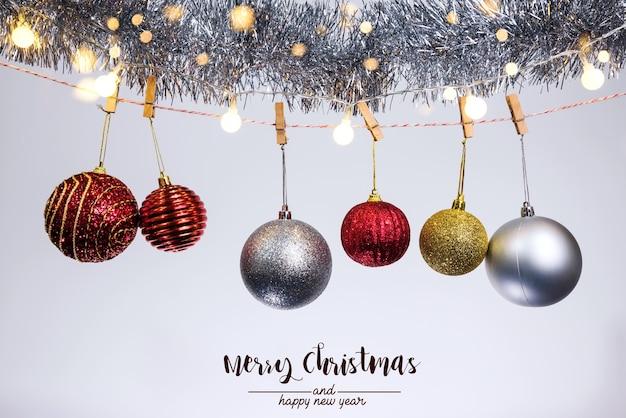 Bombki choinkowe i ozdoby na abstrakcyjnym tle bokeh na białym tle. karta z pozdrowieniami tło wakacje na boże narodzenie i nowy rok. wesołych świąt