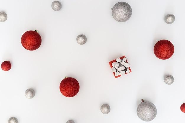 Bombki choinkowe ozdoby czerwone i srebrne kulki i pudełko na białym tle