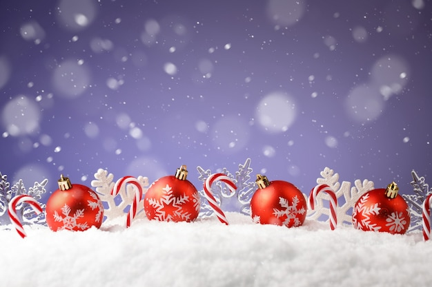 Bombki choinkowe, płatki śniegu i cukierki w zaspie