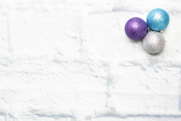 Bombki choinkowe w kolorze srebrnym i niebieskim na jasnym tle cegły. skopiuj miejsce leżał płasko.