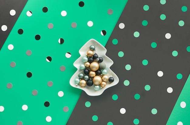 Bombki choinkowe w kształcie białego kwadratu w kształcie jodły na warstwowym zielonym, czarnym papierze, widok z góry, modne tło