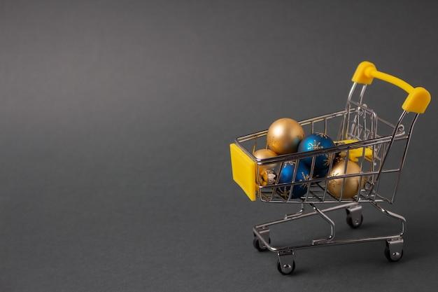 Bombki choinkowe w mini wózku na zakupy na koncepcję festiwalu bożego narodzenia i nowego roku