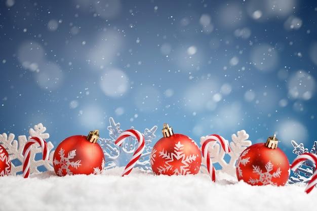 Bombki choinkowe z płatki śniegu i cukierki na niebieskim tle, kopia przestrzeń