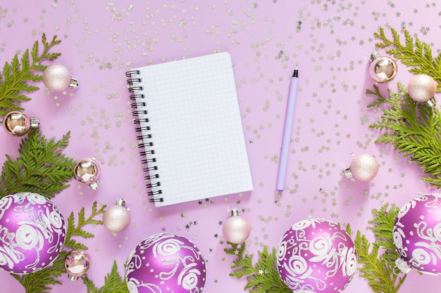 Bombki i gałązki tui na liliowym tle z brokatowymi srebrnymi gwiazdkami i otwartym spiralnym notatnikiem z długopisem