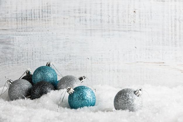 Bombki na śniegu i drewnianym tle