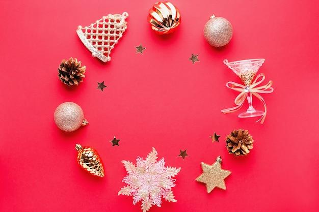 Bombki, ozdoby złote i różowe okrągłe ramki, konfetti na czerwonym tle z miejsca kopiowania. kartka świąteczna z ozdobami, widok z góry