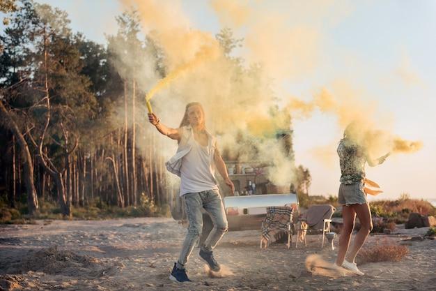 Bomby po pikniku. kilku podróżników w trampkach po pikniku, trzymając bomby ogniowe