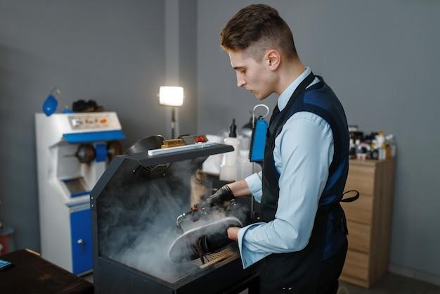 Bootmaker przetwarza obuwie na specjalnej maszynie, serwis obuwia. umiejętności rzemieślnicze, warsztat szewski, mistrz szewstwa, warsztat szewski