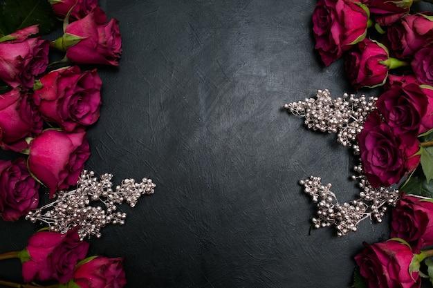 Bordowe lub wino czerwone róże i srebrny wystrój na ciemnym tle. dekoracja w stylu gotyckim. kopiuj koncepcję przestrzeni