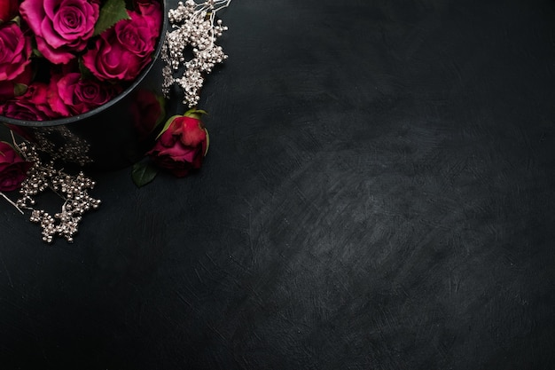 Bordowe lub wino czerwone róże i srebrny wystrój na ciemnym tle. prawdziwa miłość, pasja i pragnienie. kopiuj koncepcję przestrzeni