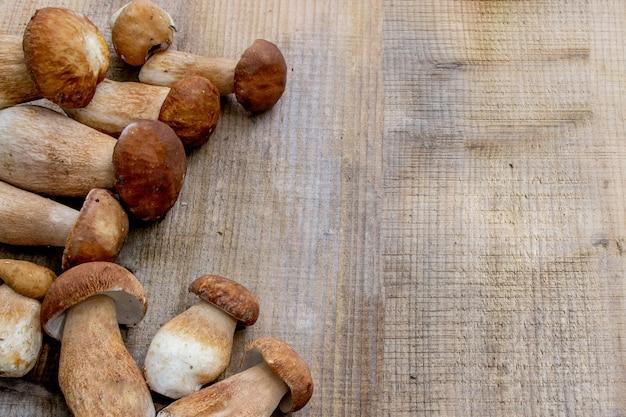 Borowik na drewnianym tle. grzyby jesienne cep. ceps boletus edulis na drewniane tła, z bliska na drewnianym stole w stylu rustykalnym. gotowanie pysznych ekologicznych grzybów. wyśmienite jedzenie.
