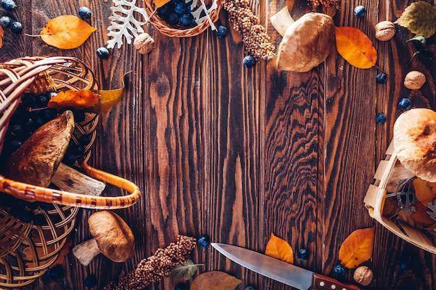 Borowiki w koszu z jagodami i orzechami na drewnianym stole. jesienne zbiory zebrane w lesie. zebrany plon jesienny. przestrzeń