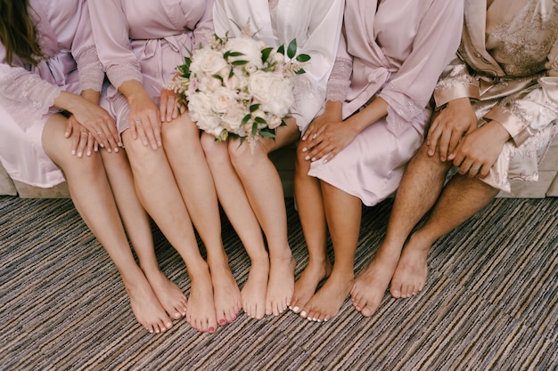 Bose stopy druhen i panny młodej z bukietem kwiatów