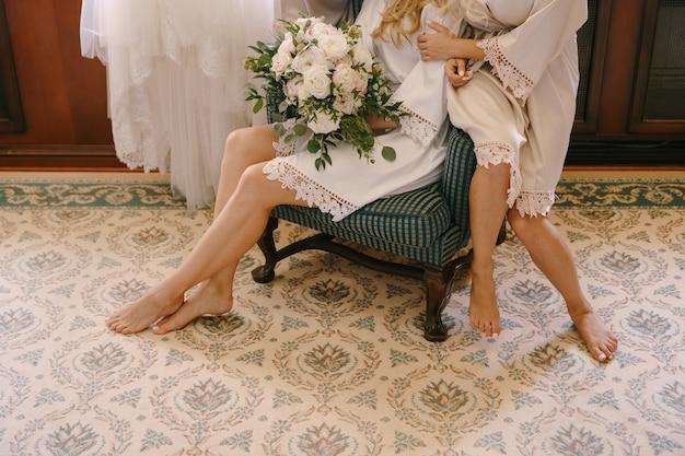 Bose stopy druhen w szatach siedzących na fotelu z bukietem kwiatów