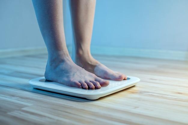 Bose stopy kobiet stoją na podłodze elektronicznej wagi, aby sprawdzić wagę ciała i kontrolować zestaw zbędnych kilogramów w niebieskim świetle