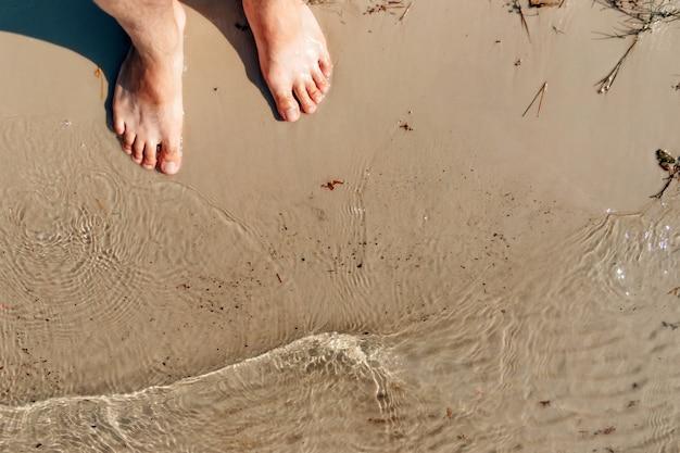 Bose stopy na żółtym morskim piasku, fala. widok z góry. wakacje, lato, wakacje, wakacje na morzu, lato. copyspace.