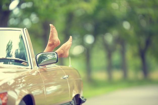 Bose stopy wystają z zabytkowego samochodu cabrio zaparkowanego w naturze.