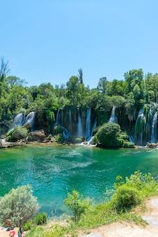 Bośnia i hercegowina, lyubushki. turyści odpoczywają i pływają w malowniczym wodospadzie. kravica.