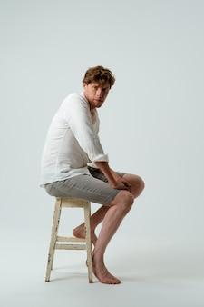 Boso człowiek pełnej wysokości siedzi na krześle. widok z boku młodego faceta w białej koszuli i dżinsach na białym tle