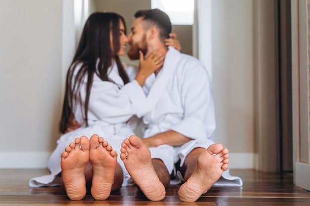 Boso kobieta i mężczyzna siedzi na podłodze w domu