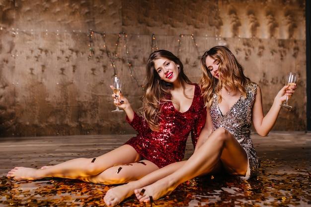 Boso kobiety w imprezowych sukienkach siedzą na podłodze po imprezie