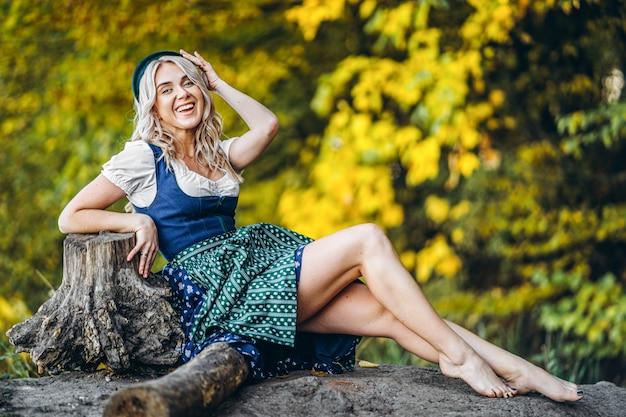 Boso szczęśliwa ładna blond dziewczyna w dirndl, tradycyjnej sukience na festiwalu piwa, siedząca na zewnątrz z blured kolorowymi drzewami za