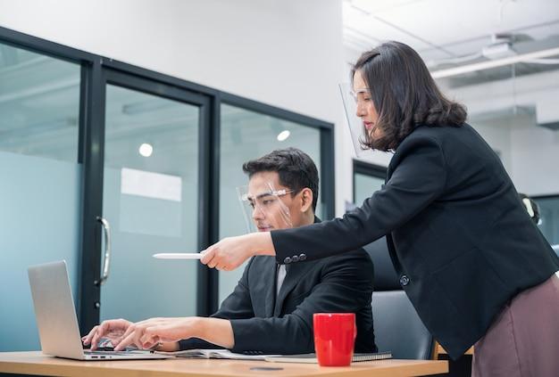 Bossy kobieta menedżer zamawiania i wskazując na laptopie pracownik płci męskiej urzędu noszenia osłony twarzy w nowym normalnym biurze