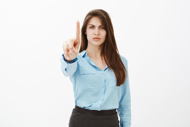 Bossy niezadowolona brunetka bizneswoman pozuje w studio
