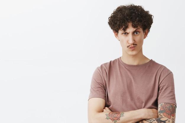 Bossy niezadowolony i podejrzliwy przystojny stylowy żyd z kręconymi włosami i wąsami w brązowej koszulce trzymający ręce skrzyżowane na piersi, uśmiechając się i marszcząc brwi z powątpiewaniem na szarą ścianę