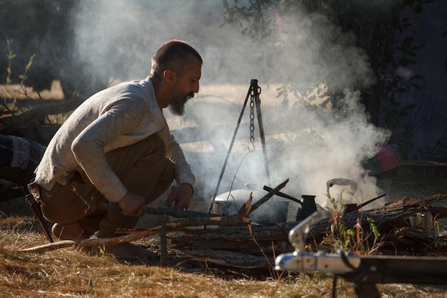 Bosy mężczyzna z brodą rozpala ogień pod kociołkiem, aby rozpocząć gotowanie