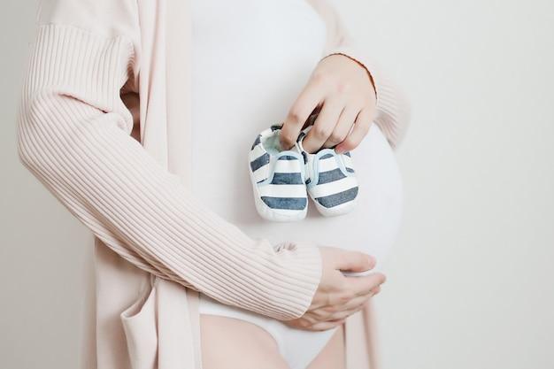 Botki w rękach przyszłej mamy z brzuchem w ciąży