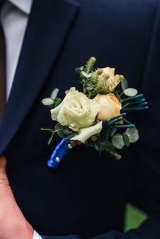 Boutonniere z białą różą na klapie niebieskiej kurtki pana młodego