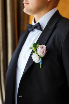 Boutonniere z różowej róży, eustomy i zieleni przymocowane do czarnego smokingu pana młodego