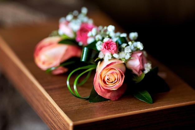 Boutonniery z różowych róż i zieleni leżą na stole